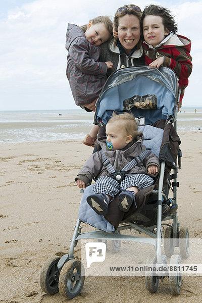Mutter mit drei Kindern am Strand