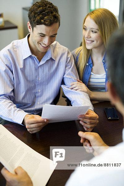 Paar Überprüfung der Unterlagen im Gespräch mit dem Berater