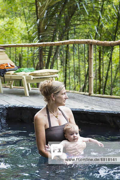 Caucasian mother and baby relaxing in pool