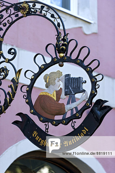 Wrought iron hanging sign  photographer with a historical camera with bellows  Burghausen  Upper Bavaria  Bavaria  Germany