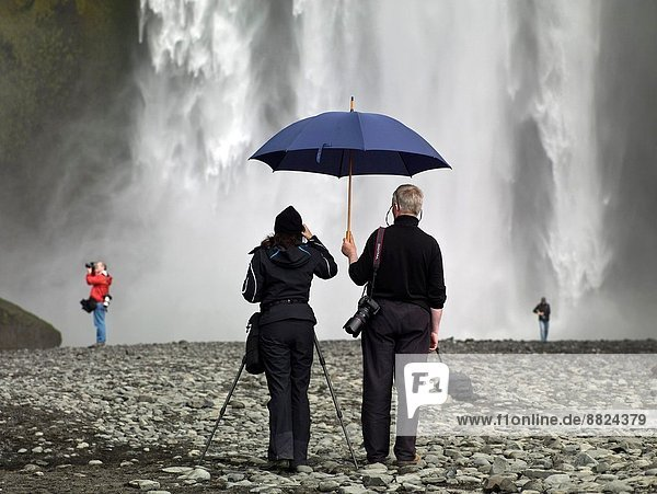 Taking pictures at Skogafoss Waterfalls  Iceland