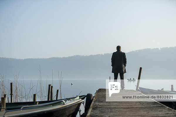 Mann steht auf Holzsteg und schaut auf den See.