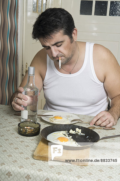 Portrait of man with bad habit sitting at breakfast table