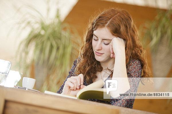 Junge Frau mit Notizbuch-Schriftzug im Cafe