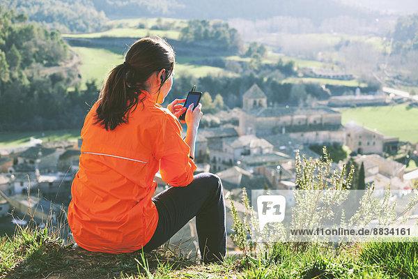 Spanien  Katalonien  Orista  junge Joggerin bei einer Pause mit Smartphone