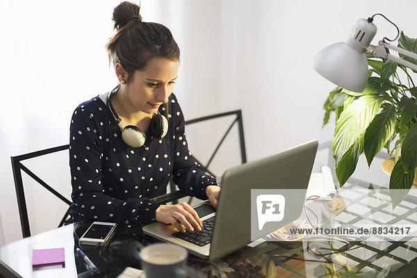 Young woman working with laptop at home