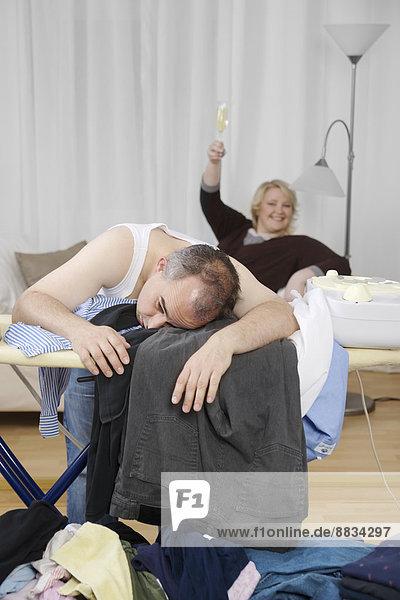 Erschöpfter Mann am Bügelbrett mit Frau im Hintergrund