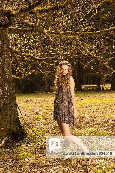 Romantische junge Frau im Park stehend