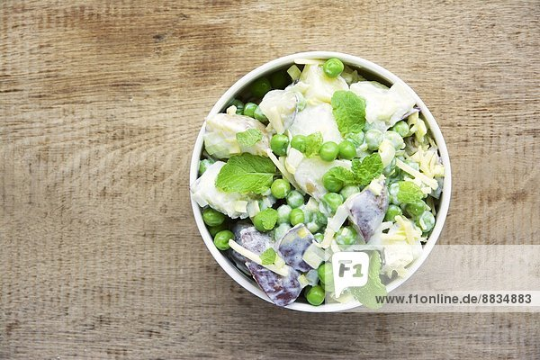 Minted pea and potato salad in bowl Minted pea and potato salad in bowl