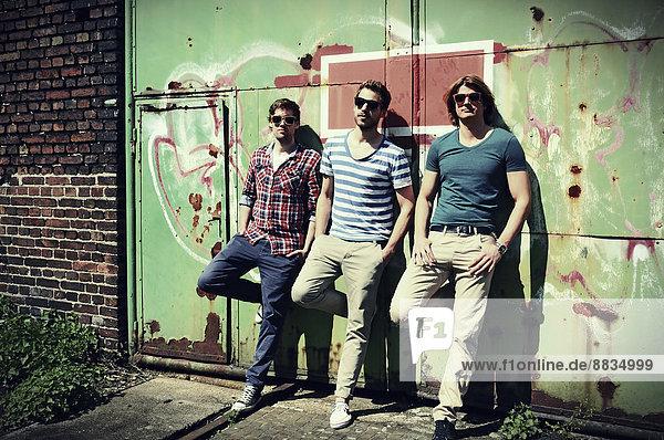 Drei junge Männer warten vor dem alten Industriegebäude