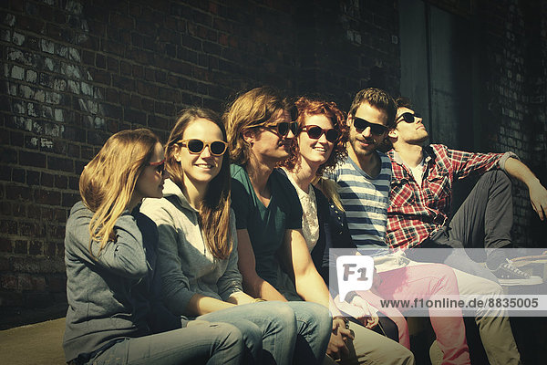 Gruppe von sechs Freunden  die vor einem alten Industriegebäude warten.
