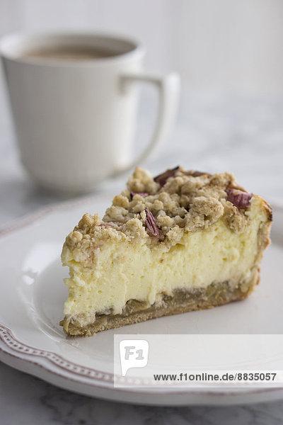 Stück Rhabarber-Käsekuchen auf Teller mit Tasse Kaffee