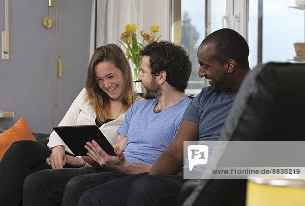 Drei Freunde haben Spaß mit dem Tablet-Computer zu Hause