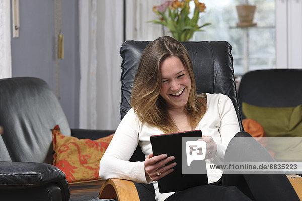 Junge Frau mit Spaß am Tablet-Computer zu Hause
