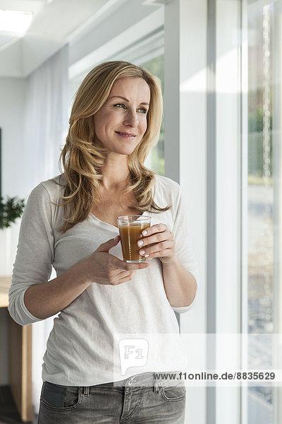 Porträt einer glücklichen Frau mit einem Getränk in ihrem hellen  modernen Zuhause.