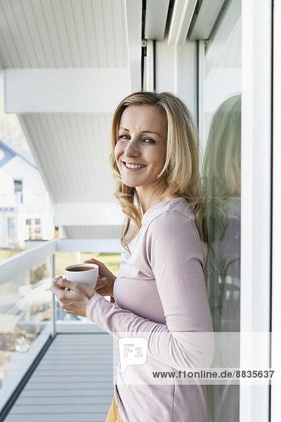 Lächelnde Frau steht auf dem Balkon ihres Hauses mit einer Tasse Kaffee.