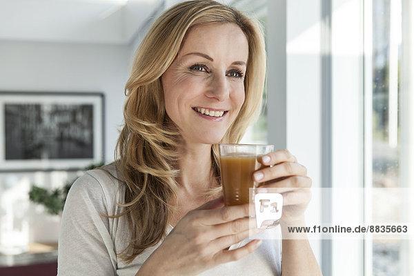 Porträt einer glücklichen Frau mit Getränk in ihrem hellen  modernen Zuhause