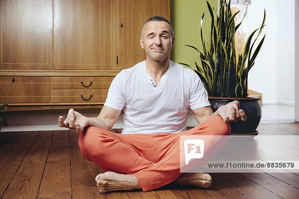 Reifer Mann in Yogastellung  der auf dem Holzboden seines Hauses sitzt.