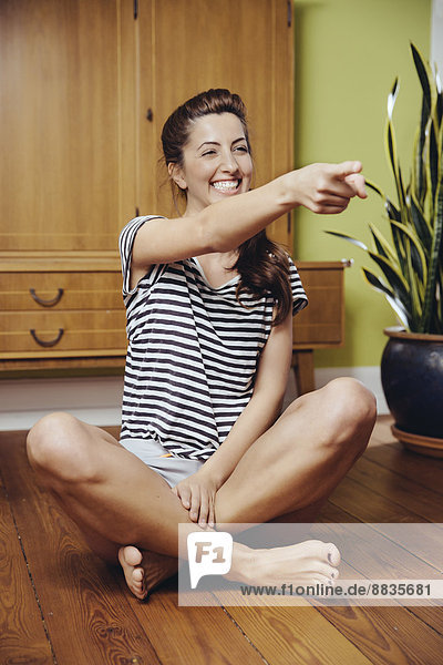Young woman sitting cross-legged on the wooden floor of her home  pointing at somebody