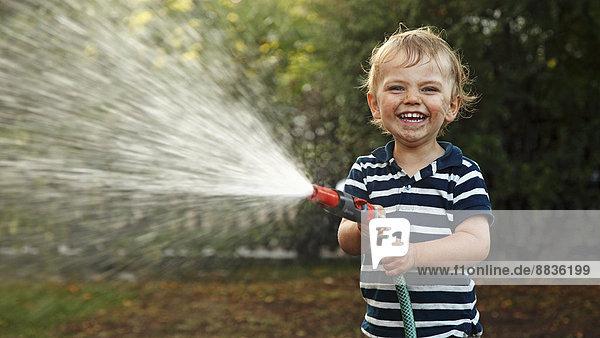 Porträt eines kleinen Jungen mit Gartenschlauch
