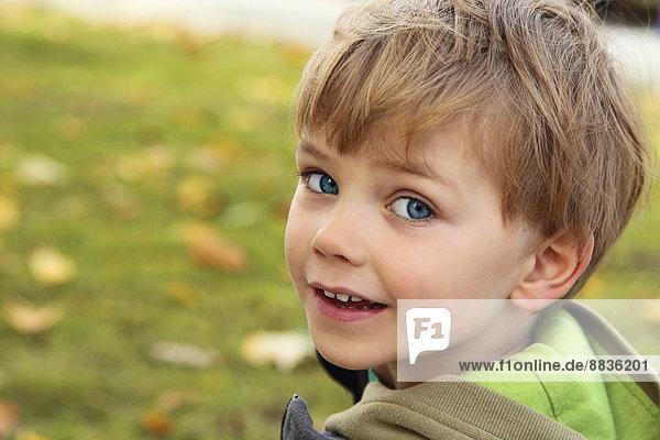 Porträt eines lächelnden kleinen Jungen  der über die Schulter schaut.
