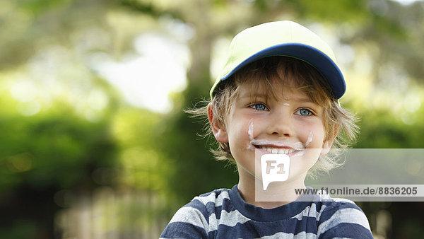 Porträt eines lächelnden kleinen Jungen mit Milchbart