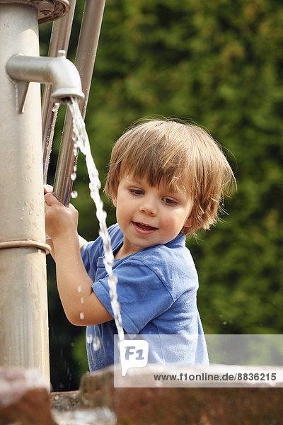 Porträt eines kleinen Jungen  der mit einer Wasserpumpe spielt.