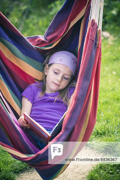 Porträt eines kleinen Mädchens mit Lesebuch in der Hängematte Porträt eines kleinen Mädchens mit Lesebuch in der Hängematte
