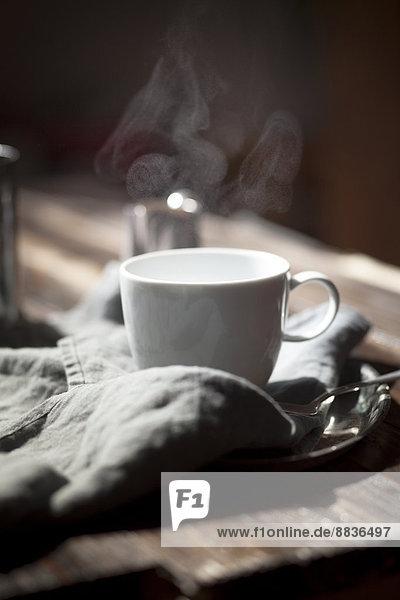 Tasse dampfender Tee auf Silberteller und Holztisch
