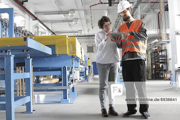 Techniker und Ingenieur in einer Fabrikhalle