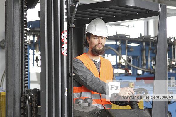 Arbeiter mit Schutzhelm in einer Fabrikhalle  der Gabelstapler fährt