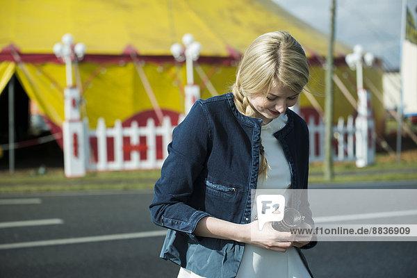 Junge Frau mit Kamera vor dem Zirkuszelt