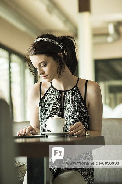 Porträt einer jungen Frau mit Tablet-Computer im Cafe