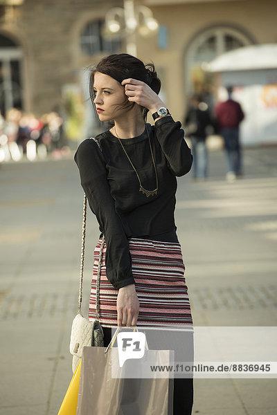 Portrait einer jungen Frau mit Einkaufstaschen