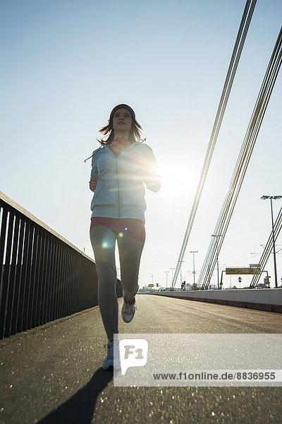 Junge Joggerin unterwegs auf einer Brücke