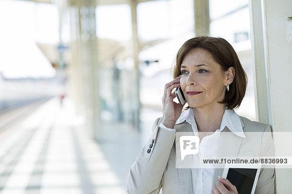 Portrait einer Geschäftsfrau beim Telefonieren auf der Plattform