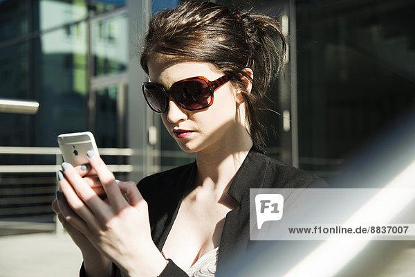 Portrait einer jungen Geschäftsfrau mit Smartphone