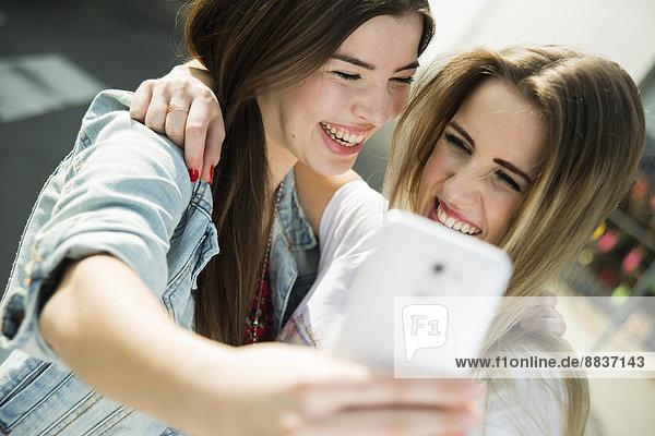 Zwei glückliche junge Frauen  die mit einem Selfie nach draußen gehen.