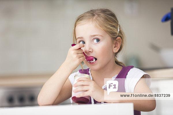 Porträt eines kleinen Mädchens beim Joghurtessen