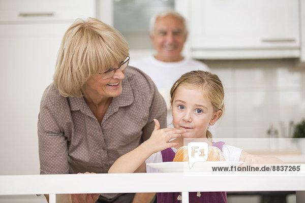 Seniorenpaar mit Enkelin in der Küche
