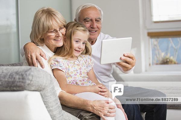 Seniorenpaar und Enkelin beim Betrachten des digitalen Tabletts zu Hause