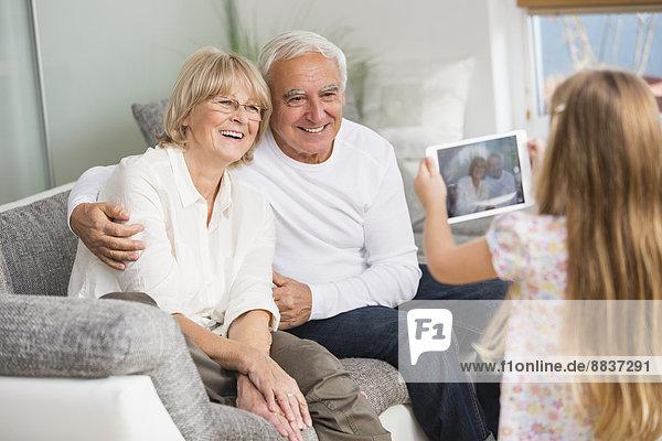 Kleines Mädchen fotografiert ihre Großeltern mit digitalem Tablett zu Hause.