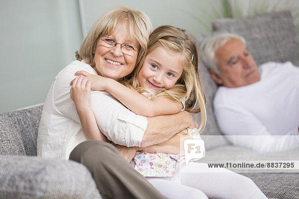 Porträt einer älteren Frau  die ihre Enkelin auf dem Sofa im Wohnzimmer umarmt.