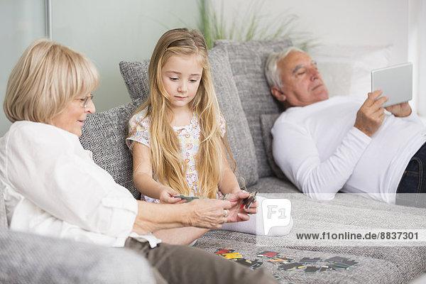 Seniorin und Enkelin beim gemeinsamen Spielen auf dem Sofa im Wohnzimmer