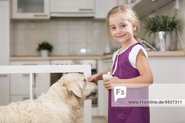 Little girl feeding dog with yogurt