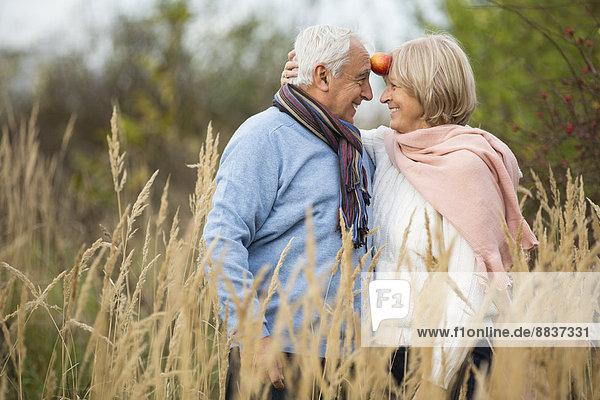 Porträt eines glücklichen Seniorenpaares mit Apfelspaß