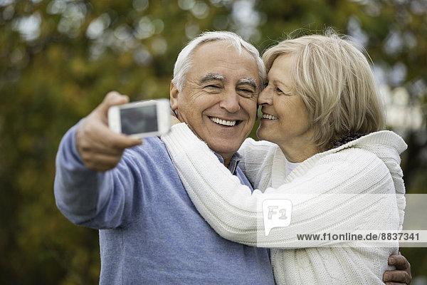 Portrait of happy senior couple taking self-portrait with smartphone