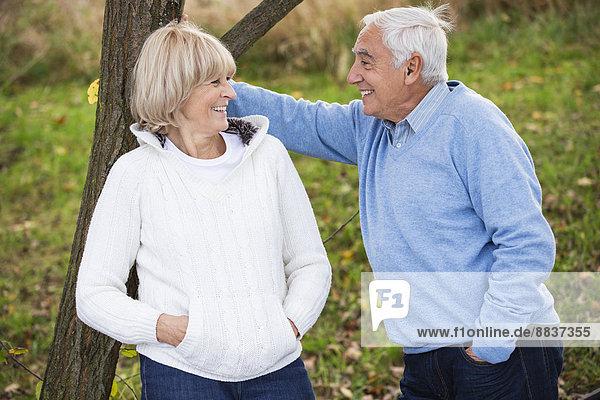 Lächelndes älteres Paar  das sich an den Baumstamm lehnt