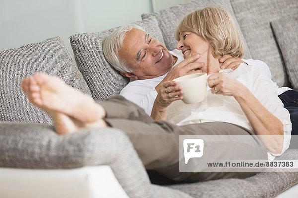 Verliebtes Seniorenpaar auf Sofa im Wohnzimmer