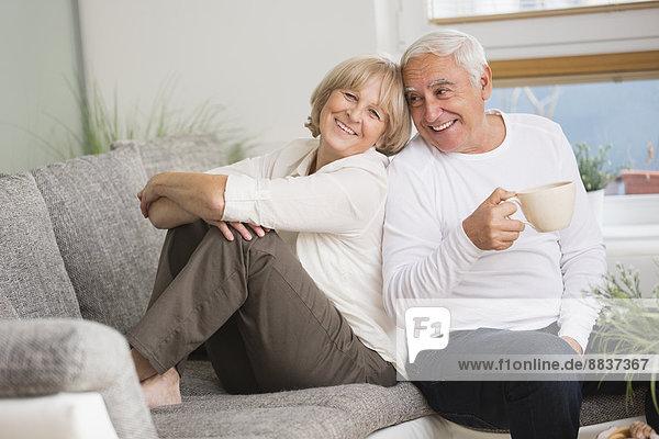 Lächelndes Seniorenpaar Seite an Seite auf dem Sofa im Wohnzimmer